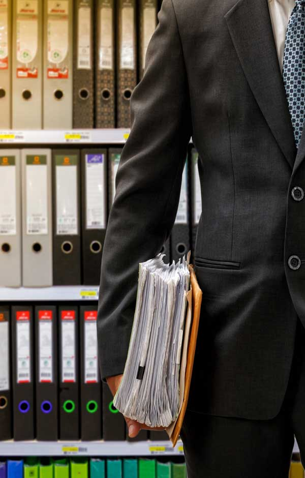 Accountant with files from the bookkeeping archive room